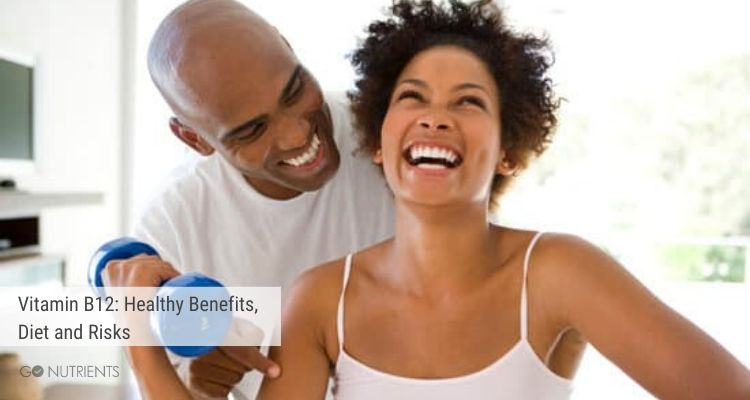 Man and woman laughing.  She is holding an exercise weight.  Vitamin B12 plays a role in good health.