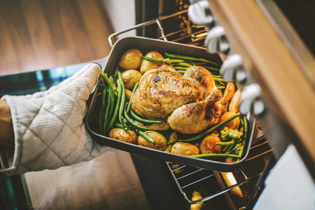 Cook taking ready fried baked chicken with vegetables from the oven. Healthy cooking concept.