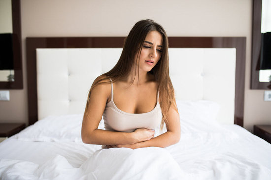 Woman sitting on edge of her bed holding her stomach from nausea.