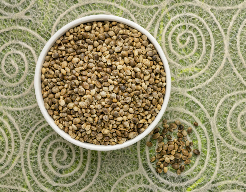 dry hemp seeds in a small ceramic bowl, top view against lace paper with spiral pattern