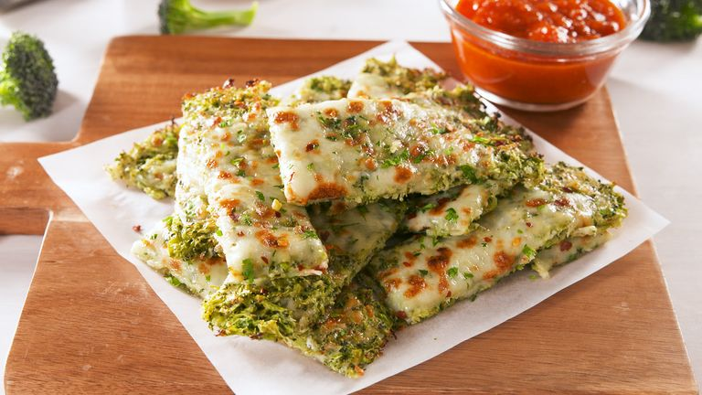 Broccoli Cheesy Bread on a white plate with a small bowl of sauce next to it.