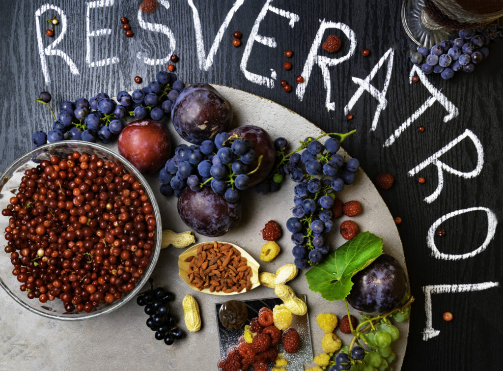 food rich with resveratrol, grapes, plums, goji, peanuts, cranberry,raspberrys dark chocolate, red wine on black wooden background