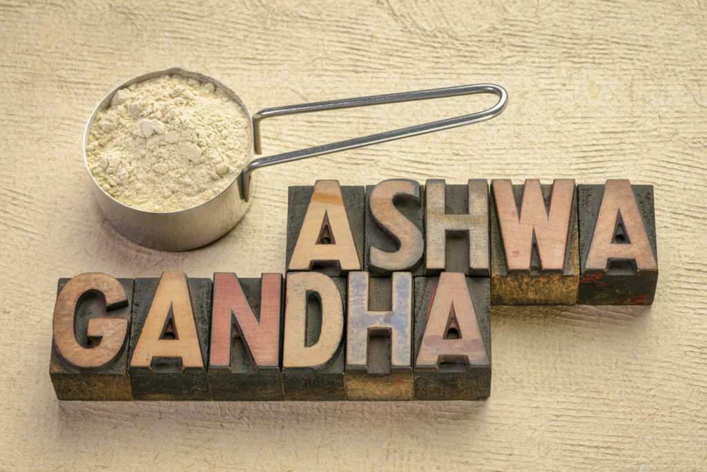 scoop of ashwagandha root (aka Indian ginseng) powder with a text in vintage letterpress wood type,